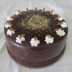 SIZE 28 CM HAZEL MERINGUE CAKE Chocolate sponge with a layer of meringue and filled with hazel nut cream and nuts.